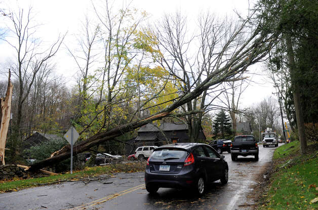 Cars travel under a large tree fallen across Main Street in Ridgefield during Hurricane Sandy, Tuesday, Oct. 30, 2012. Photo: Carol Kaliff