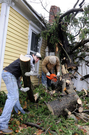 Chris Loehr, left, and his father John, clear branches that are part of a huge tree that fell onto their home in Ridgefield, Conn. during Hurricane Sandy, Tuesday, Oct. 30, 2012. Photo: Carol Kaliff