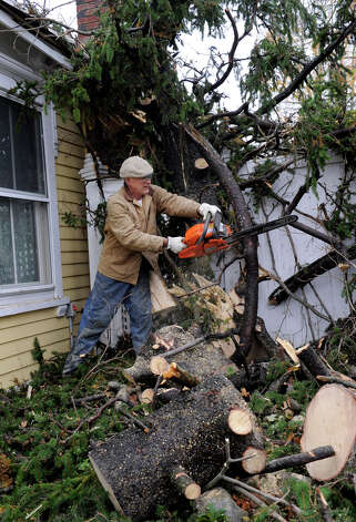 John Loehr clears branches that are part of a huge tree that fell onto his home in Ridgefield, Conn. during Hurricane Sandy, Tuesday, Oct. 30, 2012. Photo: Carol Kaliff