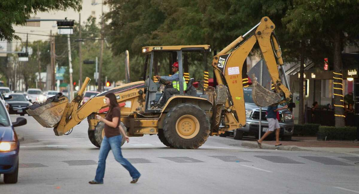 A front loader with a back hoe retires from a workday to its parking space as neighborhood walkers go to restaurants and bars, Tuesday, Oct. 23, 2012, in Houston. ( Nick de la Torre / Houston Chronicle )