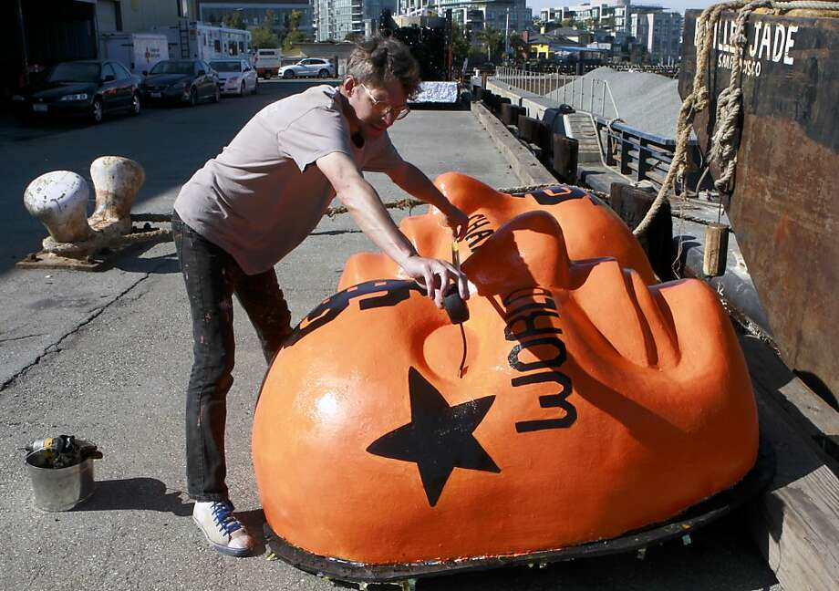Chuck Speta measures a large orange mask while he and others build floats at Pier 54 for the World Series victory parade. Photo: Paul Chinn, The Chronicle