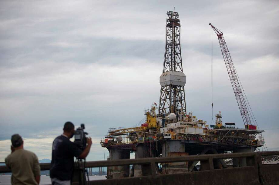 A TV crew films at an oil rig in Brazil, whose lawmakers are struggling over how to spread the profits. Photo: Felipe Dana, STR / AP