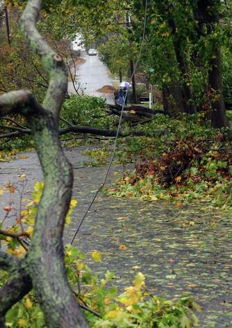 Pedestrians are viewed walking the streets of Shippan through downed trees and wire on Tuesday, October 30, 2012. Photo: Lindsay Niegelberg