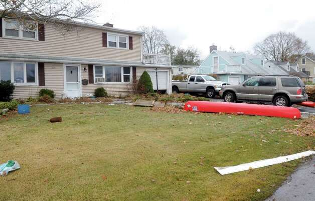 A canoe and a kayak are strewn on a lawn in the Cove area of Stamford on Tuesday, October 30, 2012. Photo: Lindsay Niegelberg