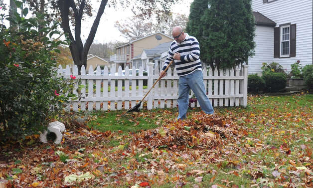 Mike Young rakes debris from Hurricane Sandy on Derwen Street in Stamford on Tuesday, October 30, 2012. Photo: Lindsay Niegelberg