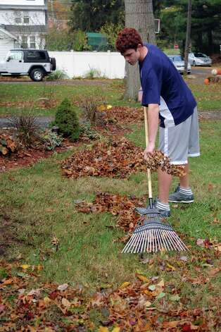 Jack Young, 14, rakes debris from Hurricane Sandy on Derwen Street in Stamford on Tuesday, October 30, 2012. Photo: Lindsay Niegelberg