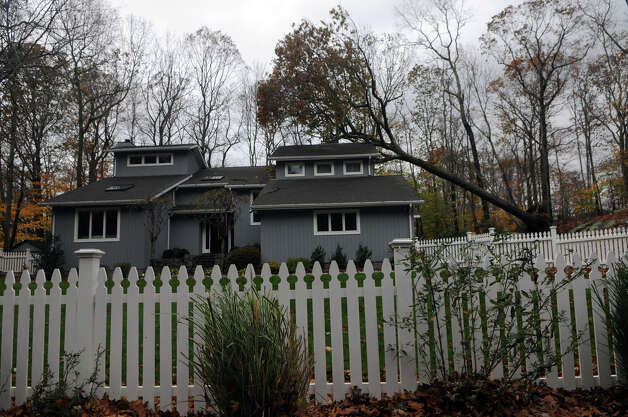 A tree rests on the home of Mark Bennet and Katie Meyers after Hurricane Sandy related weather in North Stamford, Conn., Oct. 30, 2012. Photo: Keelin Daly