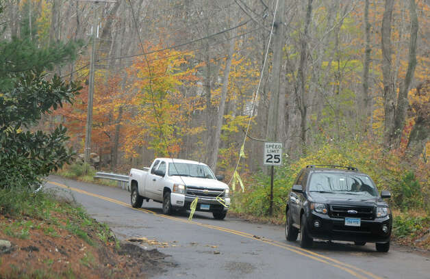 Drivers pass under a broken power line on Brookdale Road after Hurricane Sandy related weather in Stamford, Conn., Oct. 30, 2012. Photo: Keelin Daly