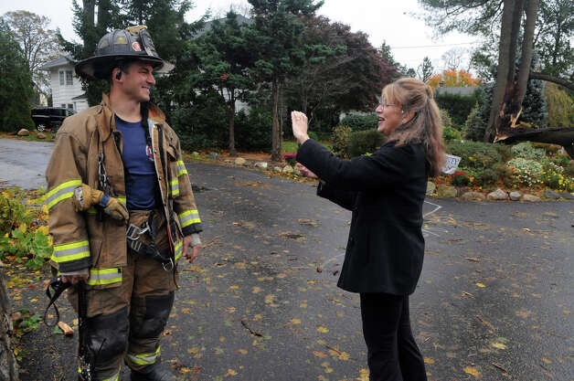 Merry Flaherty takes a shot of Stamford Fire and Rescue Firefighter Tony Marino as she documents the aftermath of Hurricane Sandy related weather on Southfield Road in Stamford, Conn., Oct. 30, 2012. Photo: Keelin Daly