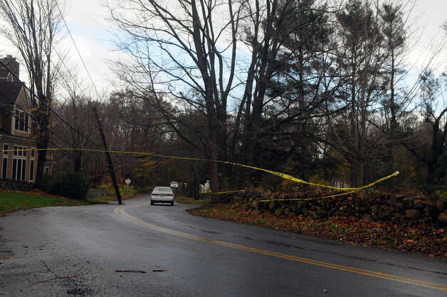 A driver ignores the police tape and passes under hanging wires along Davenport Ridge Road after Hurricane Sandy related weather passed through Stamford, Conn., Oct. 30, 2012. Photo: Keelin Daly