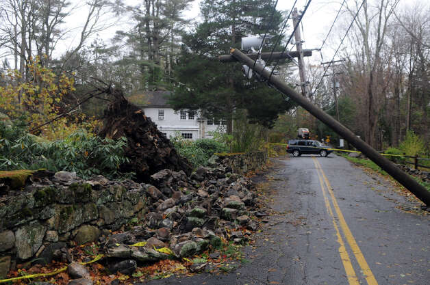 A broken pole combined with an uprooted tree which destroyed a portion of a stone wall causes a traffic closure at the intersection of Scofieldtown Road and Chestnut Hill Road after Hurricane Sandy related weather in Stamford, Conn., Oct. 30, 2012. Photo: Keelin Daly