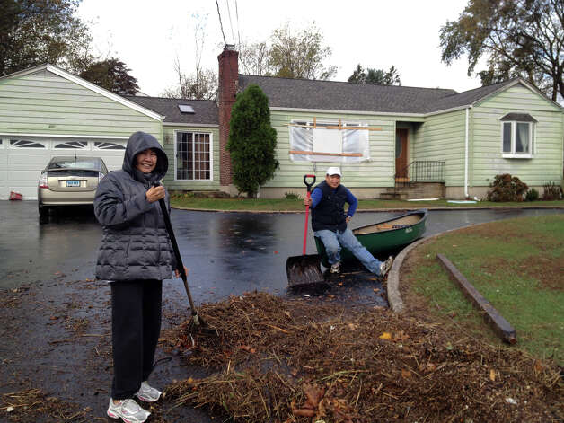 Weed Avenue residents Vicky and husband Ernesto Hermosura cleaning their driveway in Stamford, Conn.on Tuesday, Oct 30, 2012. Ernesto is sitting on a canoe that he found in his driveway, one of a half-dozen canoes that floated up from Holly Pond found in driveways, in lawns or along the guardrail on Weed Avenue. Photo: John Nickerson