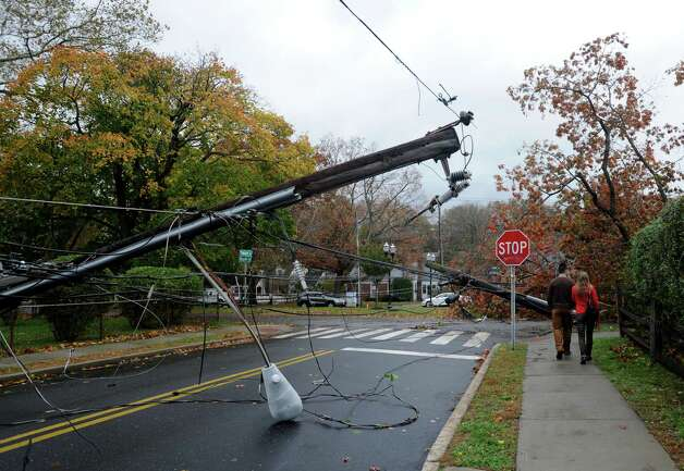 A couple walks past some downed telephone poles off Hope Street in Stamford, Conn. on Tuesday, Oct. 30, 2012. The winds from Hurricane Sandy toppled a huge tree which ripped up the sidewalk and knocked down poles in the area. Photo: Cathy Zuraw