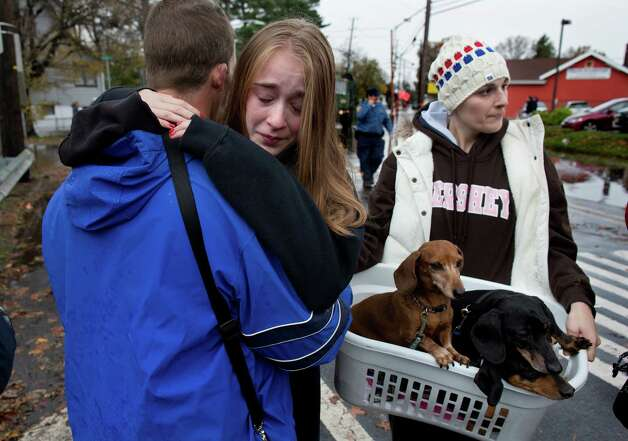 Olivia Loesner, 16, hugs her uncle, Little Ferry Deputy Fire Chief John Ruff, after she was brought from her flooded home in a boat in Little Ferry, N.J., Tuesday, Oct. 30, 2012, in the wake of superstorm Sandy. At right carrying pets, is her mother, Janice Loesner. Photo: Craig Ruttle, Associated Press / FR61802 AP