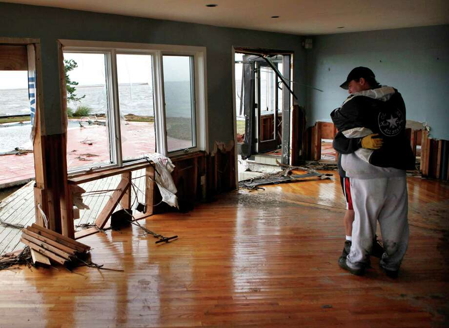 Johnny Adinolfi is comforted by neighbor John Vento, right, as he stands in what was once the living room of his home in the aftermath of superstorm Sandy, Tuesday, Oct. 30, 2012, in Massapequa, N.Y. Sandy, the storm that made landfall Monday, caused multiple fatalities, halted mass transit and cut power to more than 6 million homes and businesses. Photo: Jason DeCrow, Associated Press / FR103966 AP