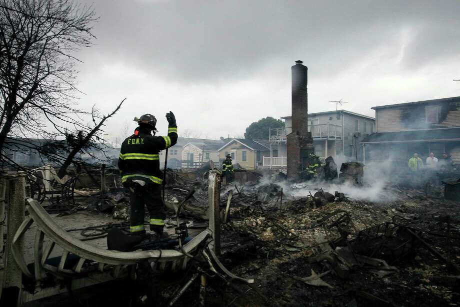 A fire fighter surveys the smoldering ruins of a house in the Breezy Point section of New York, Tuesday, Oct. 30, 2012. More than 50 homes were destroyed in a fire which swept through the oceanfront  community during superstorm Sandy. Photo: Mark Lennihan, Associated Press / AP