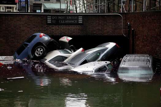 Cars are submerged at the entrance to a parking garage in New York's Financial District in the aftermath of superstorm Sandy, Tuesday, Oct. 30, 2012. New York City awakened Tuesday to a flooded subway system, shuttered financial markets and hundreds of thousands of people without power a day after a wall of seawater and high winds slammed into the city, destroying buildings and flooding tunnels. Photo: Richard Drew, Associated Press / AP