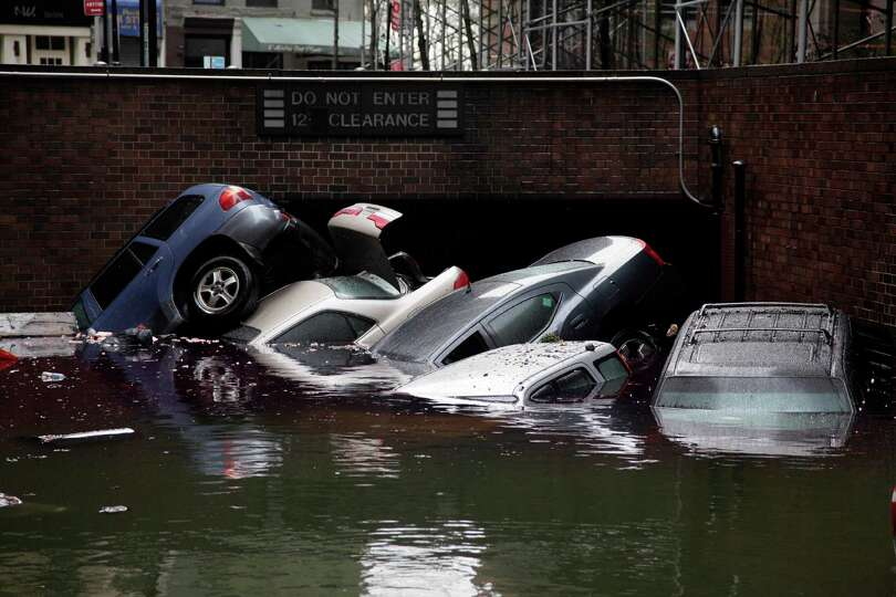 Cars are submerged at the entrance to a parking garage in New York's Financial District in the after