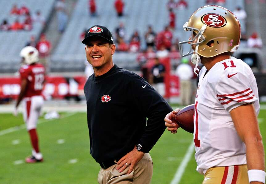 San Francisco 49ers head coach Jim Harbaugh, left, talks with quarterback Alex Smith (11) prior to a