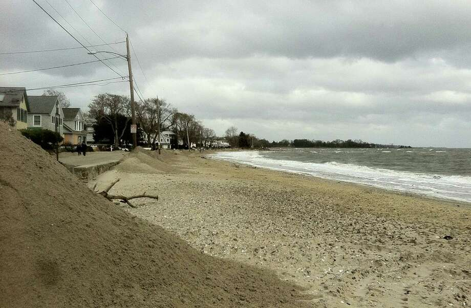 Large sections of the sand barrier built over the weekend at Compo Beach to block Hurricane Sandy flood waters were washed away by the storm overnight Monday. Photo: Paul Schott