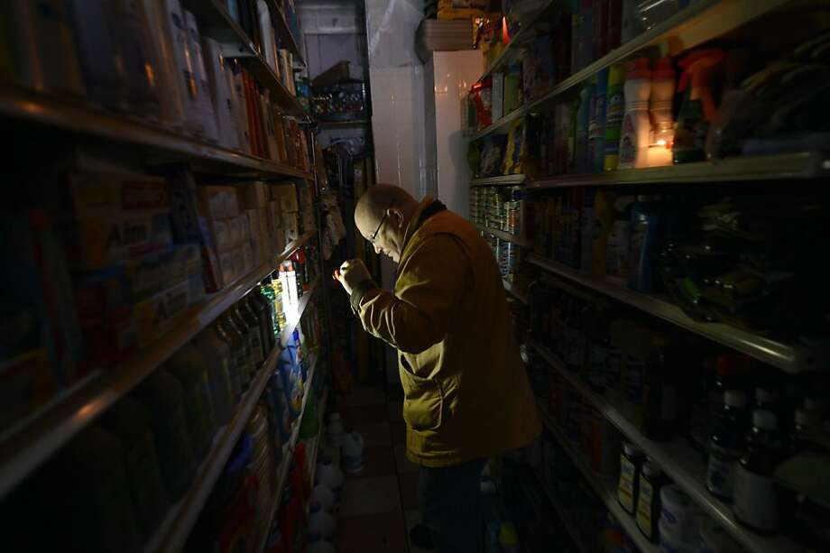 With the power still outin New York's East Village, a man has to use a flashlight to shop for groceries. Photo: Timothy A. Clary, AFP/Getty Images
