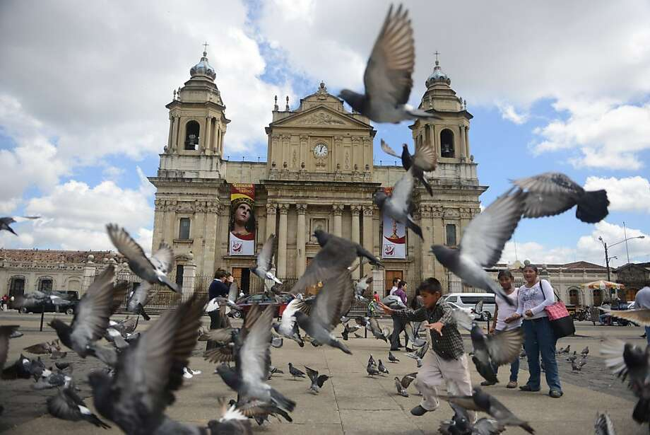 A children plays with pidgeons at the Constitucion Square on October 30, 2012 in Guatemala City. AFP PHOTO / Johan ORDONEZ/AFP/Getty Images Photo: Johan Ordonez, AFP/Getty Images