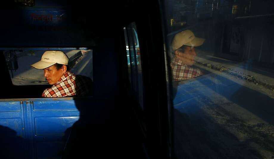 A public transport driver waits for passengers in Katmandu, Nepal, Tuesday, Oct. 30, 2012. (AP Photo/Niranjan Shrestha) Photo: Niranjan Shrestha, Associated Press