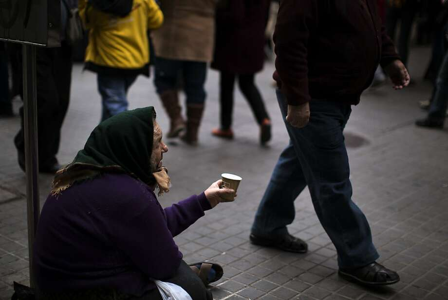 A woman begs for alms in a street in Barcelona, Spain, Tuesday, Oct. 30, 2012. Spain's National Statistics Institute says Tuesday that the country's economy contracted 0.3 percent in the third quarter from the previous three month period. Spain is in a double-dip recession and has a 25 percent unemployment rate. Prime Minister Mariano Rajoy said Monday the country has no immediate need to ask for outside aid to help deal with its debts. (AP Photo/Emilio Morenatti) Photo: Emilio Morenatti, Associated Press