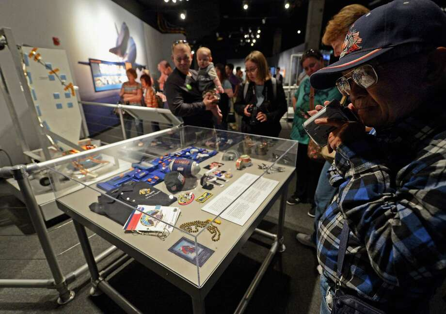 People look at an exhibit showing memrobilia from the space shuttle Endeavour after a grand opening ceremony at the new Samuel Oschin Pavilion of the California Science Center on October 30, 2012 in Los Angeles, California. Photo: Kevork Djansezian, Getty Images / 2012 Getty Images