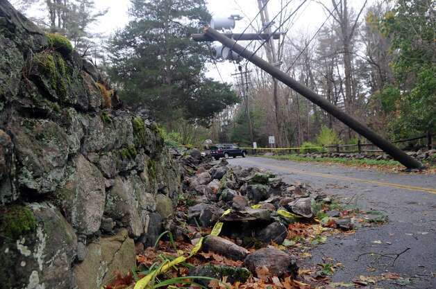 A broken pole combined with an uprooted tree which destroyed a portion of a stone wall causes a traffic closure at the intersection of Scofieldtown Road and Chestnut Hill Road after Hurricane Sandy related weather in Stamford, Conn., Oct. 30, 2012. Photo: Keelin Daly / Stamford Advocate Freelance