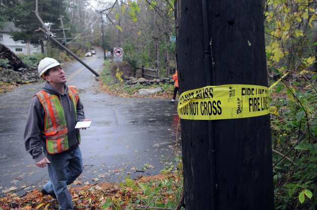 An AT&T crew assesses the broken poles at the intersection of Chestnut Hill Road and Scofieldtown Road after Hurricane Sandy related weather in Stamford, Conn., Oct. 30, 2012. Photo: Keelin Daly / Stamford Advocate Freelance