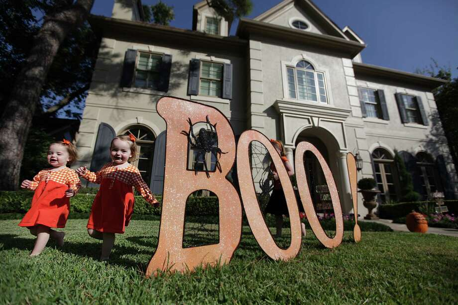 Twin sisters Hannah Thomas and Sarah Grace Thomas, 18 months, run through the front yard in their family's home in West University on Tuesday, Oct. 30, 2012, in Houston. The Thomas Family has decorated for Halloween for the last 11 years, but the decorations have gotten less gruesome after the children were born. Photo: Mayra Beltran, Houston Chronicle / Houston Chronicle