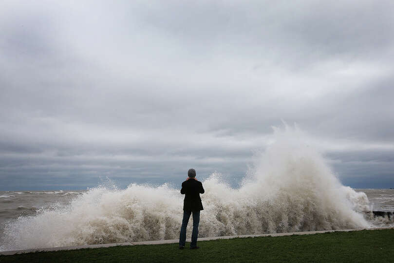 A photographer shoots waves generated from the remnants Hurricane Sandy as they crash into the
