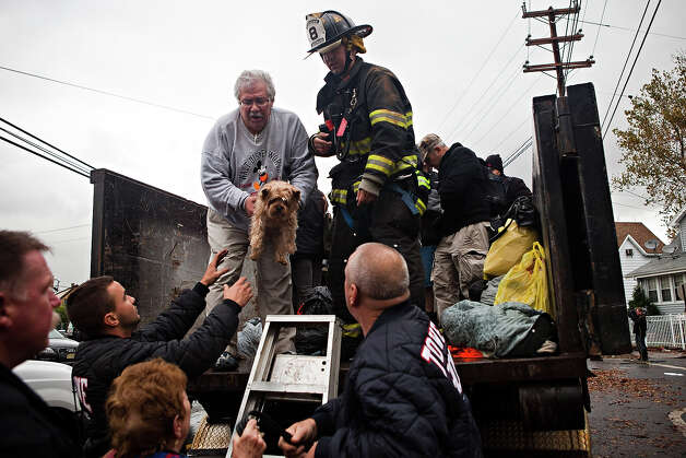 A man hands a dog to first responders while being evacuated due to flood waters caused by Hurricane Sandy on October 30, 2012 in New York City. The storm has claimed at least 40 lives in the United States, and has caused massive flooding accross much of the Atlantic seaboard. US President Barack Obama has declared the situation a 'major disaster' for large areas of the US East Coast including New York City. Photo: Andrew Burton, Getty Images / 2012 Getty Images