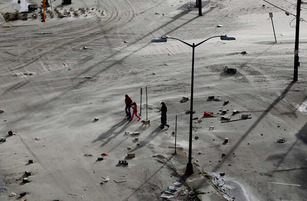 "Residents walk on a street covered in beach sand due to flooding from Hurricane Sandy on October 30, 2012 in Long Beach, New York. The storm has claimed at least 33 lives in the United States, and has caused massive flooding across much of the Atlantic seaboard. U.S. President Barack Obama has declared the situation a ""major disaster"" for large areas of the U.S. east coast, including New York City, with widespread power outages and significant flooding in parts of the city. Photo: Mike Stobe, Getty Images / 2012 Getty Images"