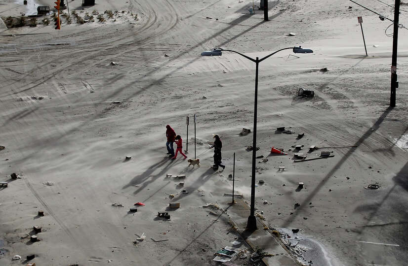 Residents walk on a street covered in beach sand due to flooding from Hurricane Sandy on October 30,