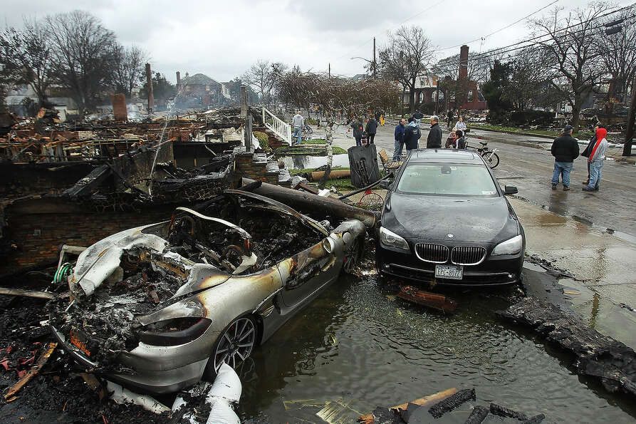 A destroyed vehicle sits near burnt homes and businesses after Hurricane Sandy on October 30, 2012 i