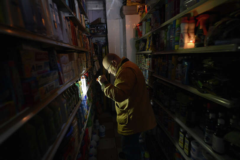 A man shops for groceries by flashlight at an East Village grocery store in New York on October 30,