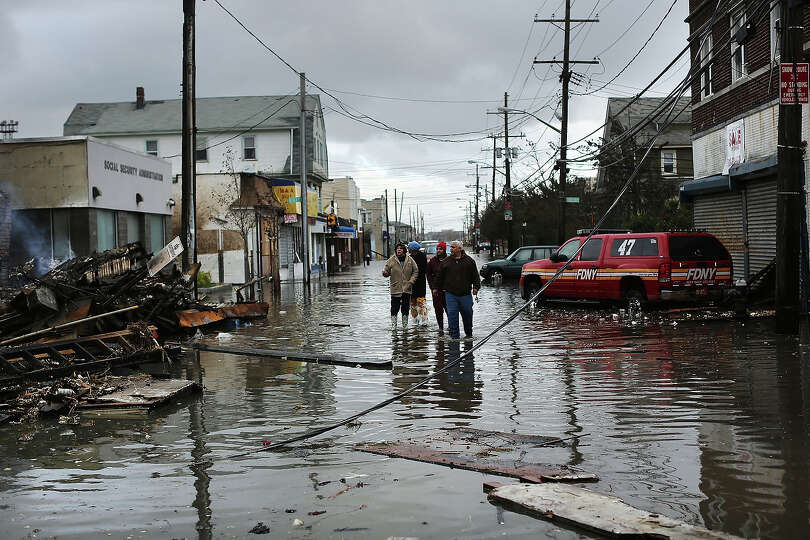 People look at homes and businesses destroyed during Hurricane Sandy on October 30, 2012 in th