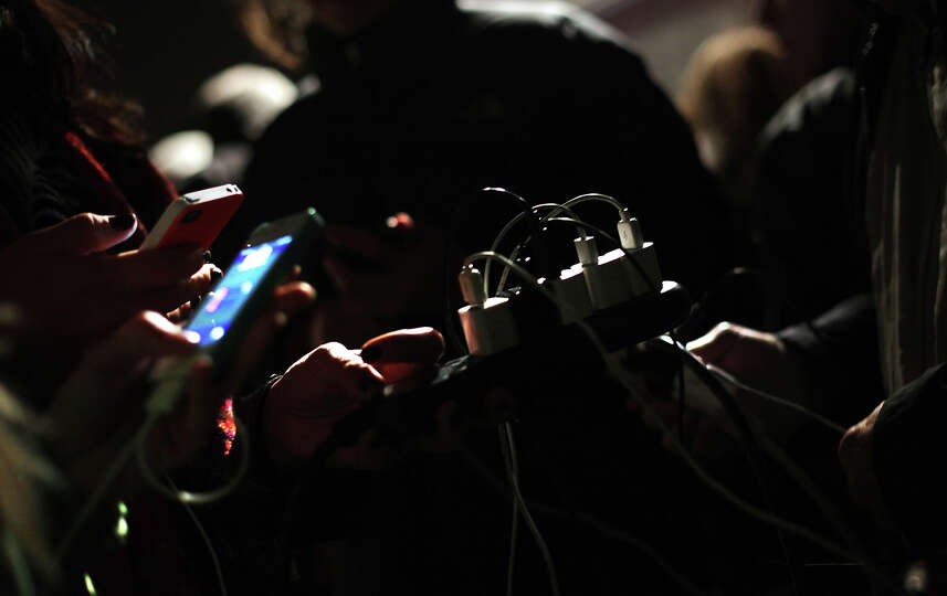 People charge their phones at a mobile charging station October 30, 2012 in New York City. The storm