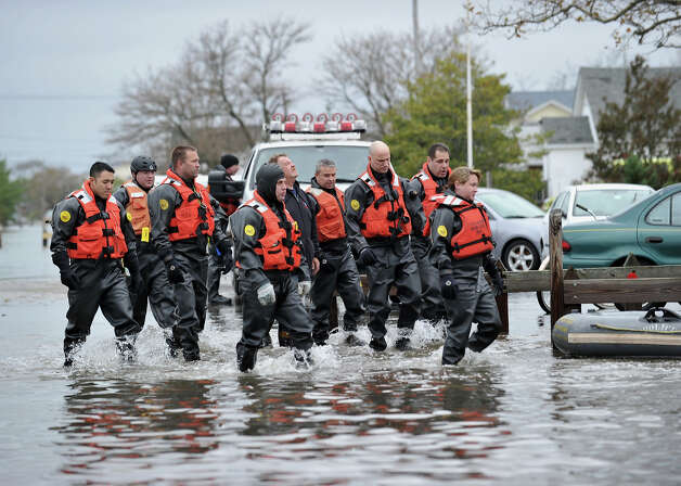 New York Police Department divers walk through a flooded area on October 30, 2012 in the Breezy Point area of Queens in New York that was hit hard by Hurricane Sandy. The death toll from superstorm Sandy has risen to 35 in the United States and Canada, and was expected to climb further as several people remained missing, officials said. Officials in the states of Connecticut, Maryland, New York, New Jersey, North Carolina, Pennsylvania, Virginia and West Virginia all reported deaths from the massive storm system, while Toronto police said a Canadian woman was killed by flying debris.  Photo: STAN HONDA, AFP/Getty Images / 2012 AFP