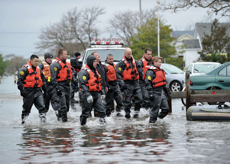 New York Police Department divers walk through a flooded area on October 30, 2012 in the Breezy Poin