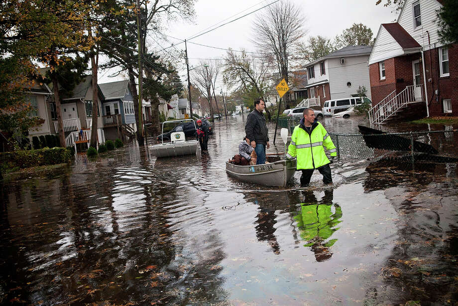 An emergency responder helps evacuate two people with a boat, after their neighborhood experienced flooding due to Hurricane Sandy, on October 30, 2012, in Little Ferry, New Jersey. The storm has claimed at least 16 lives in the United States, and has caused massive flooding accross much of the Atlantic seaboard. US President Barack Obama has declared the situation a 'major disaster' for large areas of the US East Coast including New York City. Photo: Andrew Burton, Getty Images / 2012 Getty Images