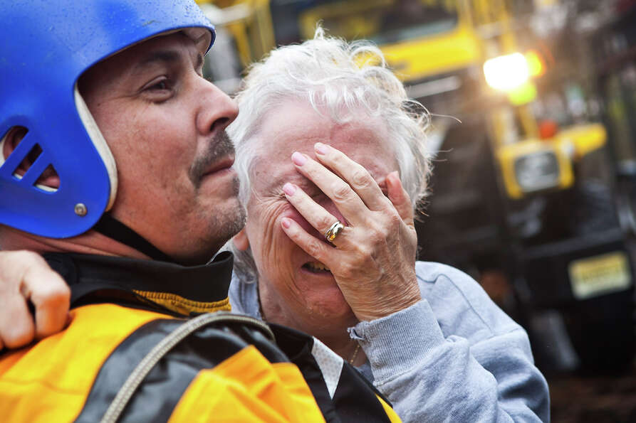 A woman cries on the shoulder of an emergency responder after being evacuated due to flooding