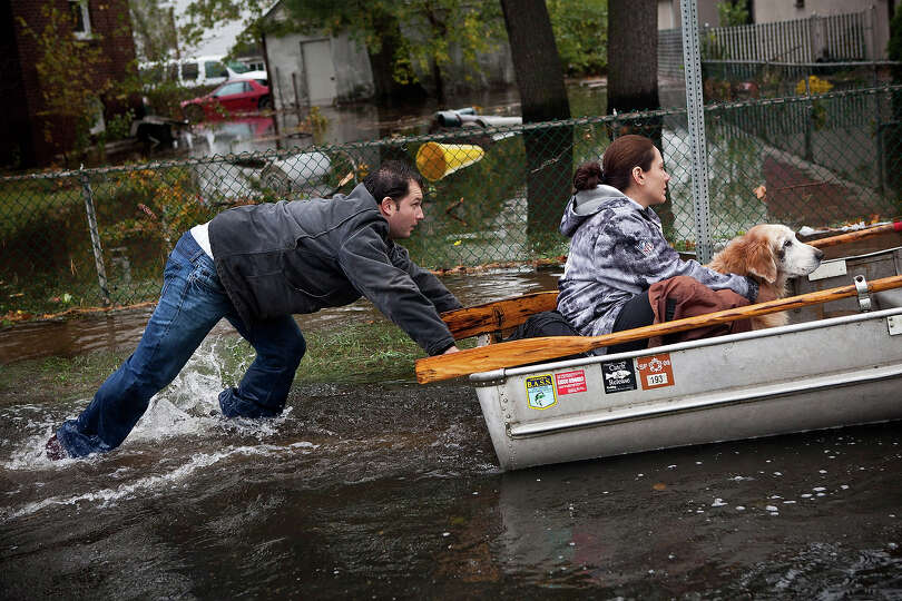 A man pushes a woman and a dog in a boat a boat after their neighborhood experienced flooding