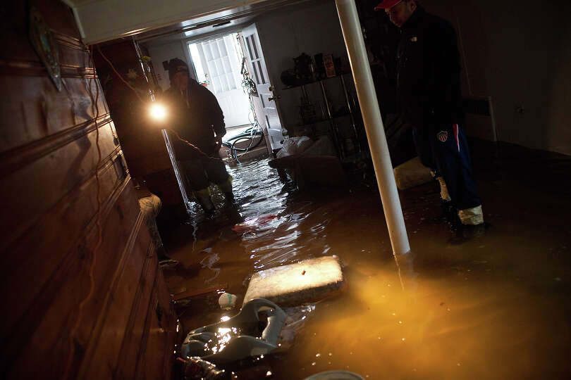 A man surveys the damage to his basement after flooding due to Hurricane Sandy, on October 30,