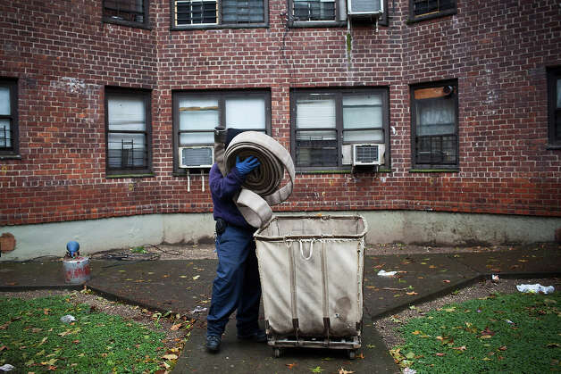 A man lifts up hosing to be used to drain a flooded basement caused by Hurricane Sandy on October 30, 2012 in the Lower East Side neighborhood of New York City. The storm has claimed at least 40 lives in the United States, and has caused massive flooding accross much of the Atlantic seaboard. US President Barack Obama has declared the situation a 'major disaster' for large areas of the US East Coast including New York City. Photo: Andrew Burton, Getty Images / 2012 Getty Images