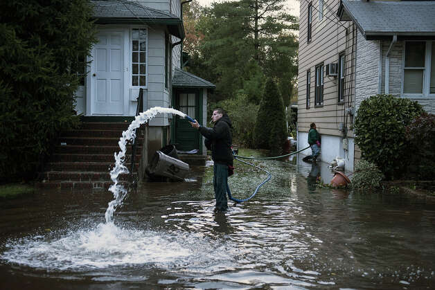 Rocky Minotti uses a pump to remove ten feet of flood water from his family's home October 30, 2012 in Little Ferry, New Jersey.  Hurricane Sandy which hit New York and New Jersey left much of Bergen County flooded and without power. Photo: BRENDAN SMIALOWSKI, AFP/Getty Images / 2012 AFP
