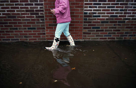 "A woman walks with ""I Love New York"" boots through flood water October 30, 2012 in Little Ferry, New Jersey.    Hurricane Sandy which hit New York and New Jersey left much of Bergen County flooded and without power.  Photo: BRENDAN SMIALOWSKI, AFP/Getty Images / 2012 AFP"