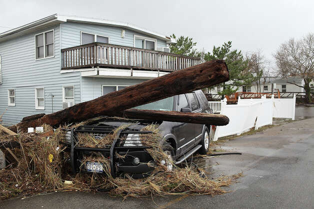 A pole sits on the hood of a SUV on October 30, 2012 in the Breezy Point Neighborhood of the Queens borough of New York City. At least 40 people were reportedly killed in the U.S. by Sandy as millions of people in the eastern United States have awoken to widespread power outages, flooded homes and downed trees. New York City was hit especially hard with wide spread power outages and significant flooding in parts of the city. Photo: Spencer Platt, Getty Images / 2012 Getty Images